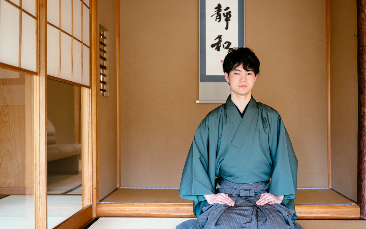 Tea master Ryo Iwamoto sitting with his legs folded in traditional Japanese style, in a Japanese tea house